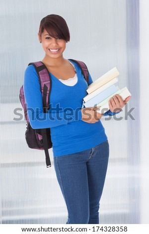 Portrait Of Happy Female Student Holding Stack Of Books - stock photo