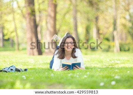 Portrait of happy female student reading a book on a nice and sunny spring day. Young woman is lying on the grass in a park and smiling to camera.