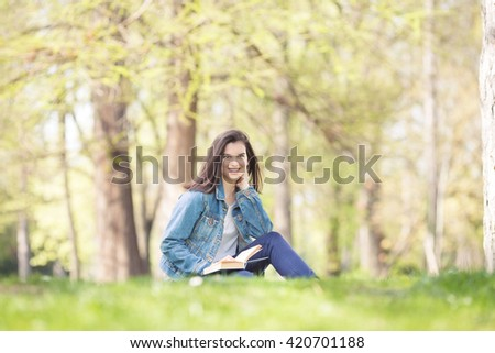 Portrait of happy female student smiling to camera. Young woman is sitting on the grass in a park and reading a book on a nice and sunny spring day. - stock photo