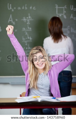 Portrait of happy female student stretching at desk with teacher in background at classroom