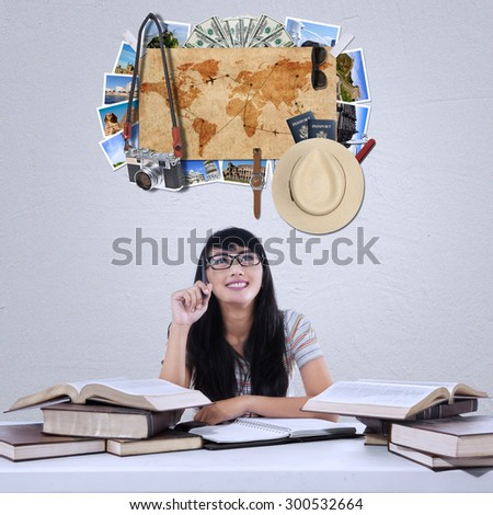 Portrait of happy female student studying with textbooks while imagine famous vacation place - stock photo