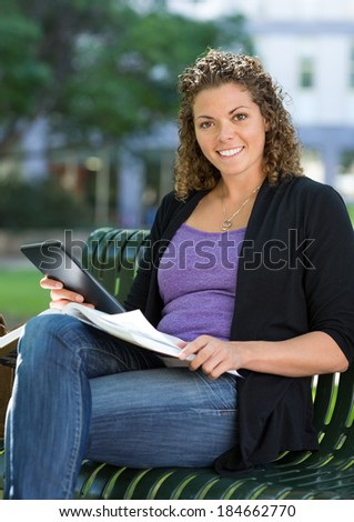 Portrait of happy female student with book and digital tablet sitting on bench at university campus