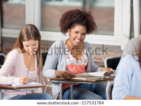 Portrait of happy female student with book sitting at desk in classroom - stock photo