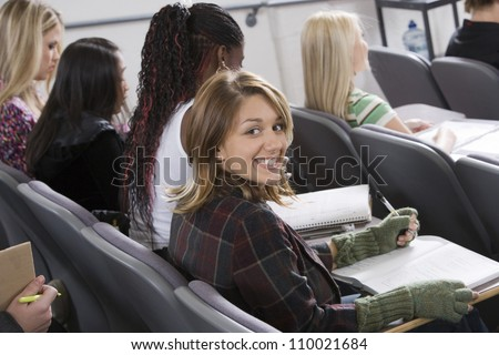 Portrait of happy female student with classmates in college