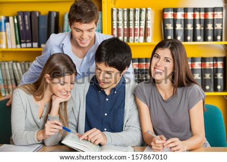 Portrait of happy female student with friends reading book in college library - stock photo