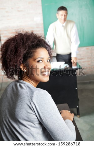 Portrait of happy female student with professor standing in background at classroom