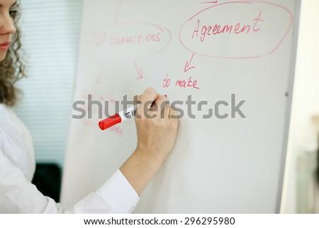 Portrait of happy female teacher writing on chalkboard - stock photo
