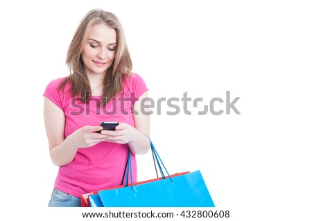 Portrait of happy female texting on cellphone while doing shopping and holding bags isolated on white with copyspace - stock photo