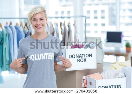 Portrait of happy female volunteer pointing to herself