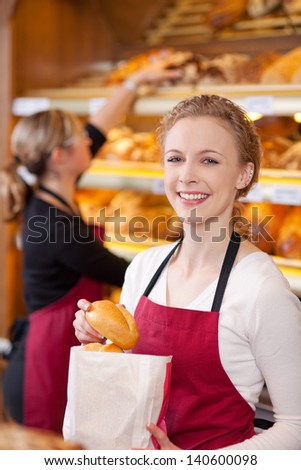 Portrait of happy female worker packing breads in bakery - stock photo