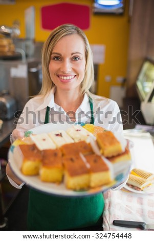Portrait of happy female worker serving pastries in plate at bakery - stock photo