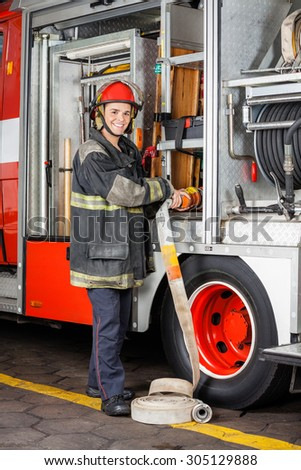 Portrait of happy firefighter adjusting hose in truck at fire station - stock photo