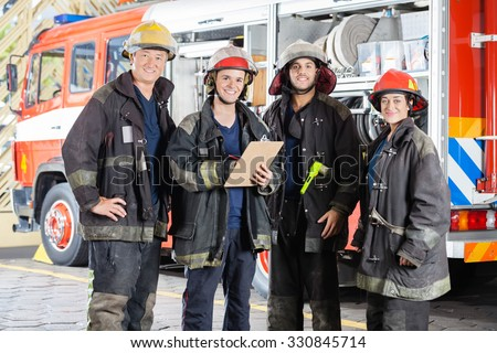 Portrait of happy firefighters standing together at fire station - stock photo
