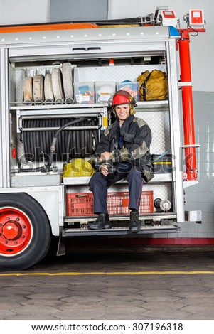 Portrait of happy fireman holding mug while sitting in truck at fire station - stock photo