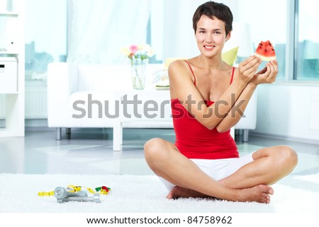 Portrait of happy fit female holding piece of watermelon - stock photo