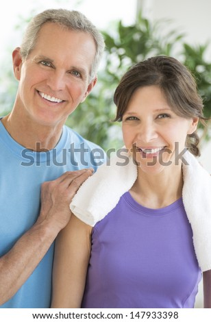 Portrait of happy fit mature couple standing together outdoors