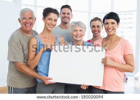 Portrait of happy fit people holding blank board in the yoga class