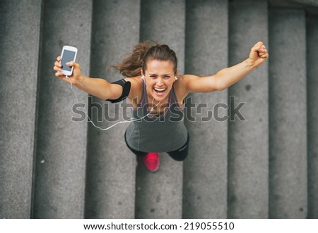 Portrait of happy fitness young woman with cell phone outdoors in the city rejoicing - stock photo