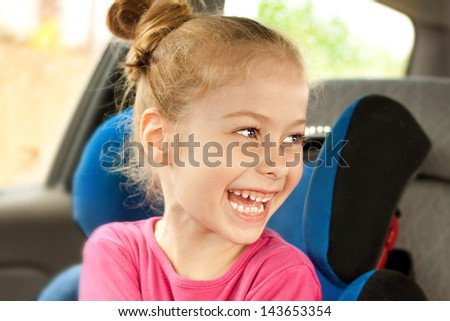 Portrait of happy five years old blond caucasian child girl laughing while traveling in a car seat - stock photo