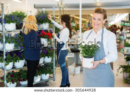Portrait of happy florist holding flower pot with colleague assisting customer in background at shop - stock photo