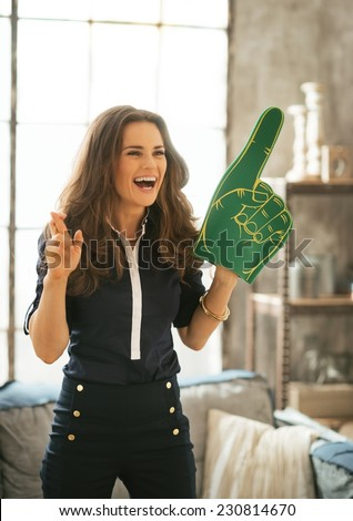 Portrait of happy football fan woman watching tv in loft apartment and cheering for - stock photo