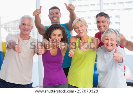 Portrait of happy friends gesturing thumbs up in fitness club - stock photo