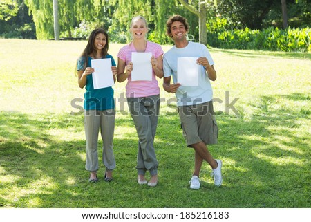 Portrait of happy friends holding blank papers on campus