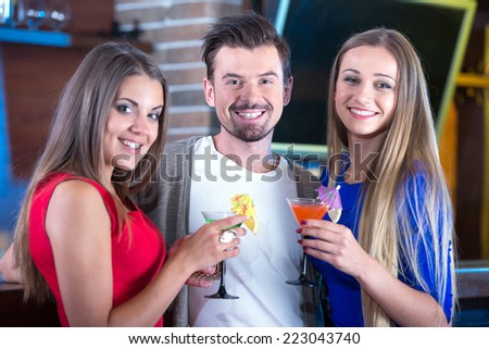 Portrait of happy friends holding glasses with cocktails in bar