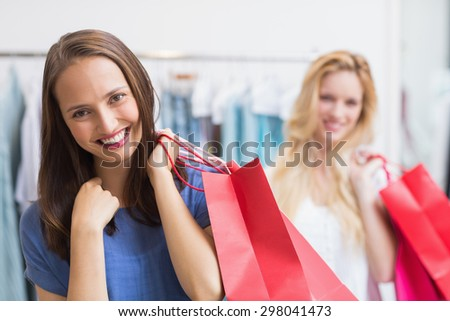 Portrait of happy friends holding shopping bags