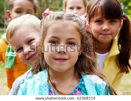 Portrait of happy friends looking at camera with pretty girl in front - stock photo