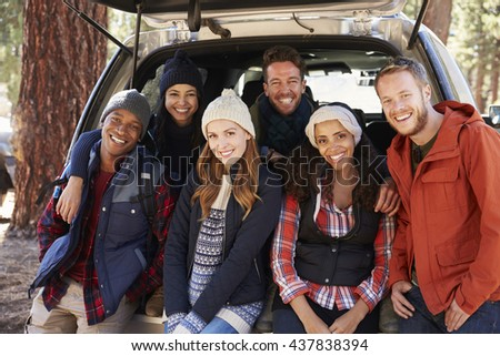 Portrait of happy friends sitting in the open back of a car
