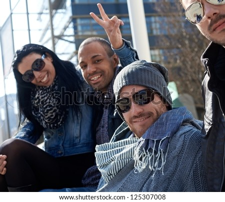 Portrait of happy friends sitting outside enjoying sunshine in springtime, looking at camera, smiling. - stock photo