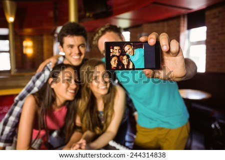 Portrait of happy friends taking a photo with a phone in a bar - stock photo
