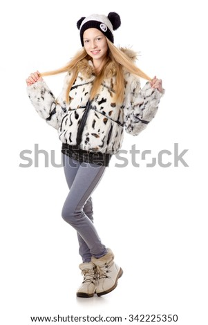 Portrait of happy funny beautiful casual caucasian teenage girl wearing winter coat and knitted hat, friendly smiling, looking at camera with cheerful expression, studio image, white background - stock photo