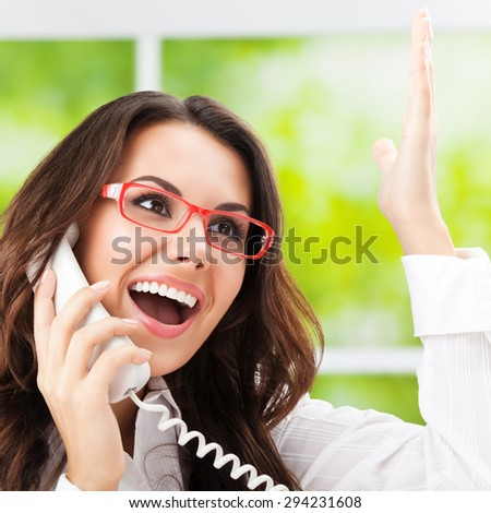Portrait of happy gesturing brunette businesswoman or support phone worker, at office - stock photo