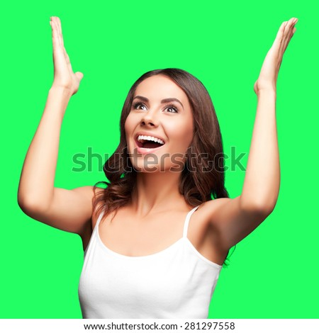 Portrait of happy gesturing or praying young beautiful woman looking up, in white casual, isolated over green screen chroma key background - stock photo