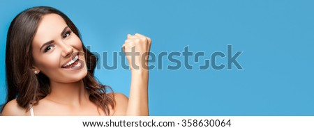 Portrait of happy gesturing smiling young beautiful woman, in white casual clothing, over blue background, with copyspace area for slogan or text - stock photo