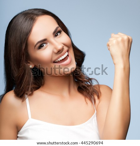 Portrait of happy gesturing smiling young beautiful woman, in white casual clothing, over grey background - stock photo