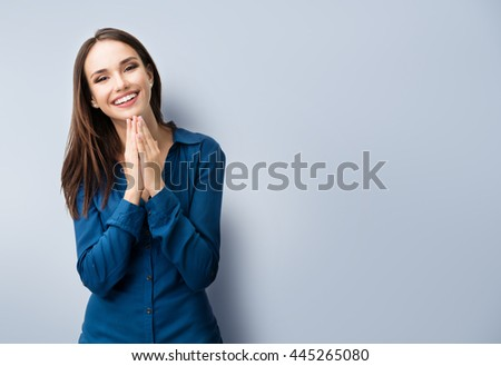 Portrait of happy gesturing smiling young woman in casual smart blue clothing, on grey, with copyspace area for text or slogan - stock photo