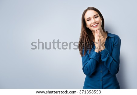 Portrait of happy gesturing smiling young woman in casual smart blue clothing, with copyspace for slogan or text message