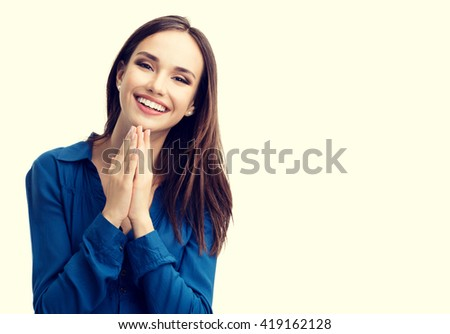 Portrait of happy gesturing smiling young woman in casual smart blue clothing, with copyspace for slogan or text message - stock photo
