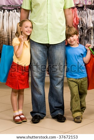 Portrait of happy girl and boy embracing their father in the mall