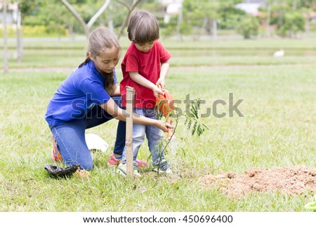 Portrait of Happy Girl and Boy Planting Outdoors