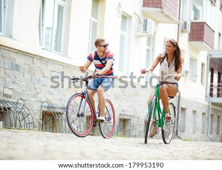 Portrait of happy girl and guy cycling at leisure - stock photo
