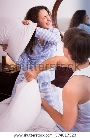 Portrait of happy girl and her boyfriend fighting on pillows