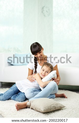 Portrait of happy girl and her mother having rest at home