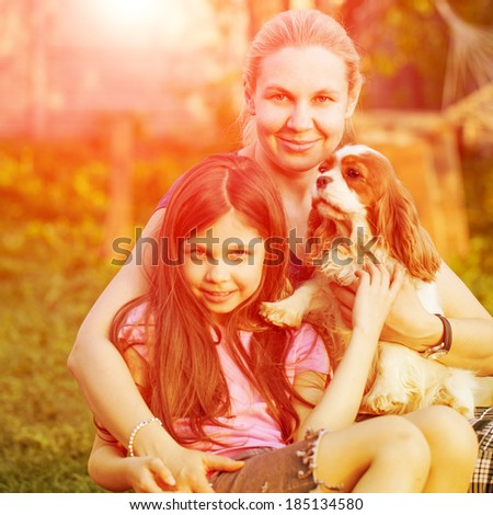 Portrait of happy girl and her mother holding dog - stock photo