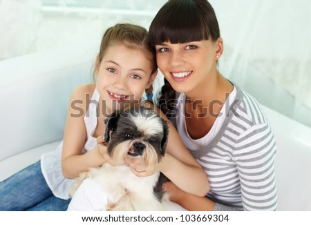 Portrait of happy girl and her mother holding pet and looking at camera