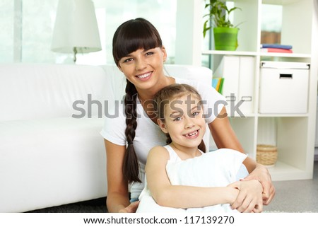 Portrait of happy girl and her mother looking at camera at home