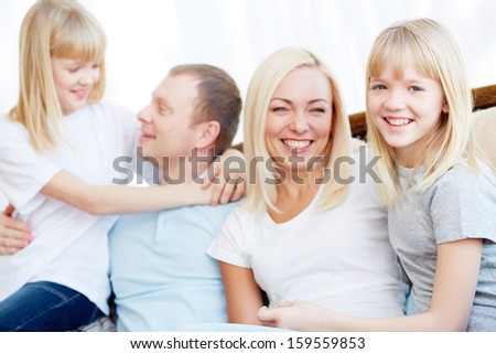 Portrait of happy girl and her mother smiling at camera on background of her father and twin sister